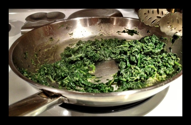 In a bit of olive oil, sweat the onions and garlic, then add the spinach, stirring it a bit to get them all coated. Put a lid on it - that'll let the steam take charge and really facilitate the steaming process!